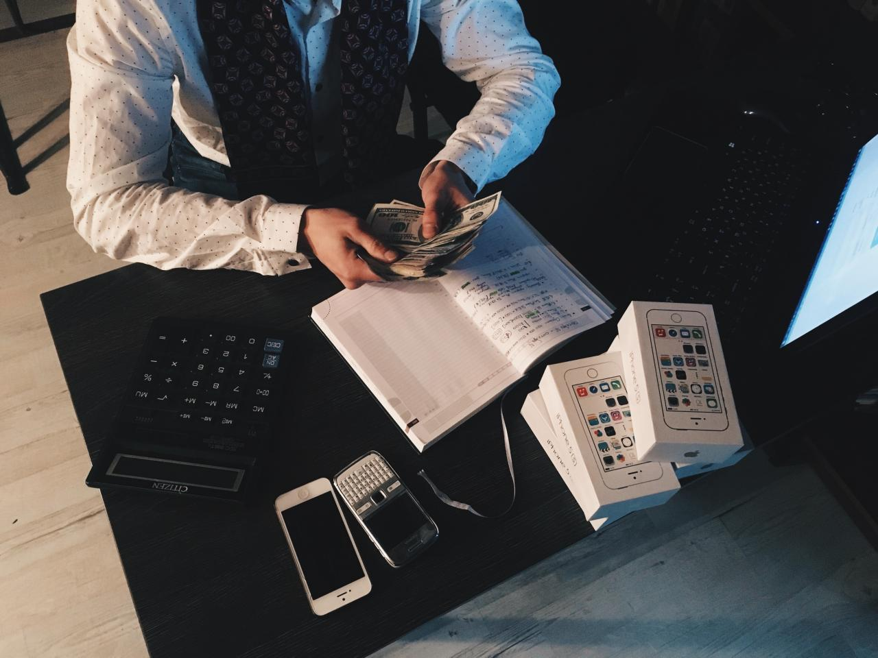 person counting money with smartphones in front on desk 3